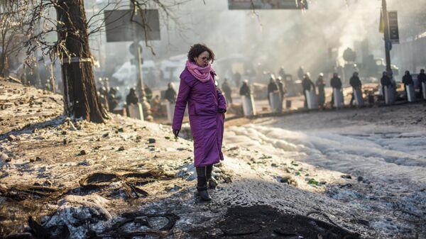Жительница Киева пытается перейти через нейтральную территорию между баррикадами оппозиции и кордоном милиции