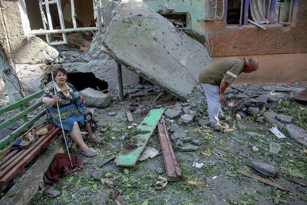 Жители разрушенного в результате артиллерийского обстрела украинскими военными многоквартирного дома в Славянске и их соседка, которая была убита, когда сидела на лавочке возле подъезда