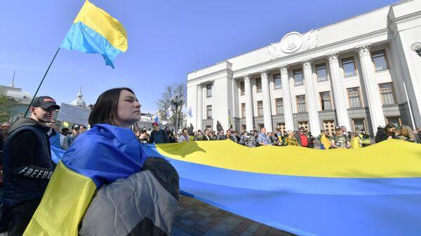 Люди c украинским флагом перед зданием парламента в Киеве