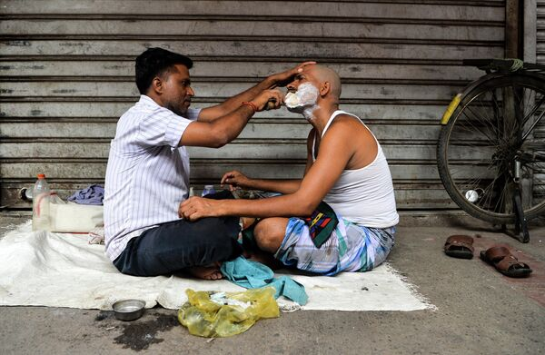 Парикмахер бреет клиента в придорожном магазине в старом квартале Нью-Дели