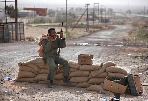 Боец с автоматом говорит по сотовому телефону на блок-посте у дороги на въезде в восточноливийский город Марса-эль-Брега, контролируемого повстанцами