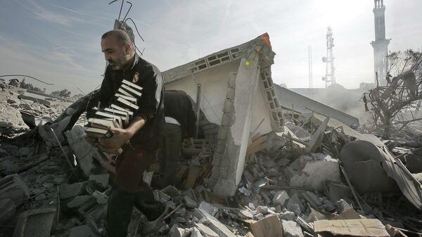 Мужчина выносит стопки Корана из разрушенного взрывом здания в Газе