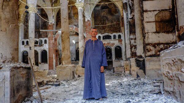 Копт в одной из сожженных и разрушенных коптских церквей в провинции Минья