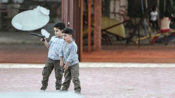 Мальчики с пистолетами играют в войну в Латакии