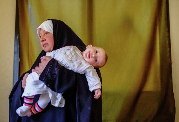 Женщина с ребенком - беженцы из Сирии - в одном из домов в городе Хальба на севере Ливана