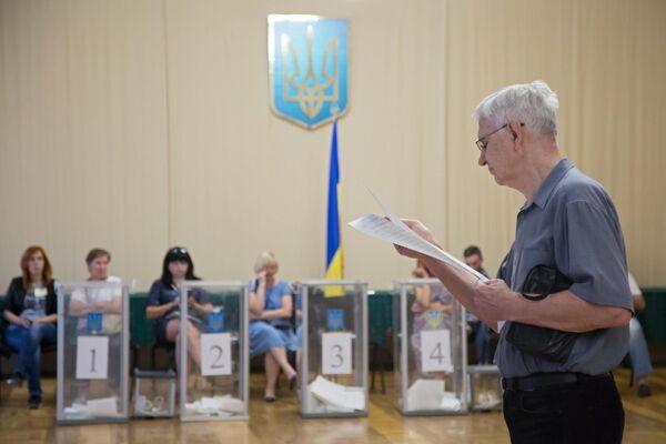 Избиратель изучает бюллетень на участке в Киеве, перед тем как проголосовать на досрочных выборах в Верховную раду Украины