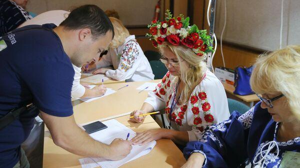 Мужчина расписывается в списке избирателей на участке в Киеве на досрочных выборах в Верховную раду Украины