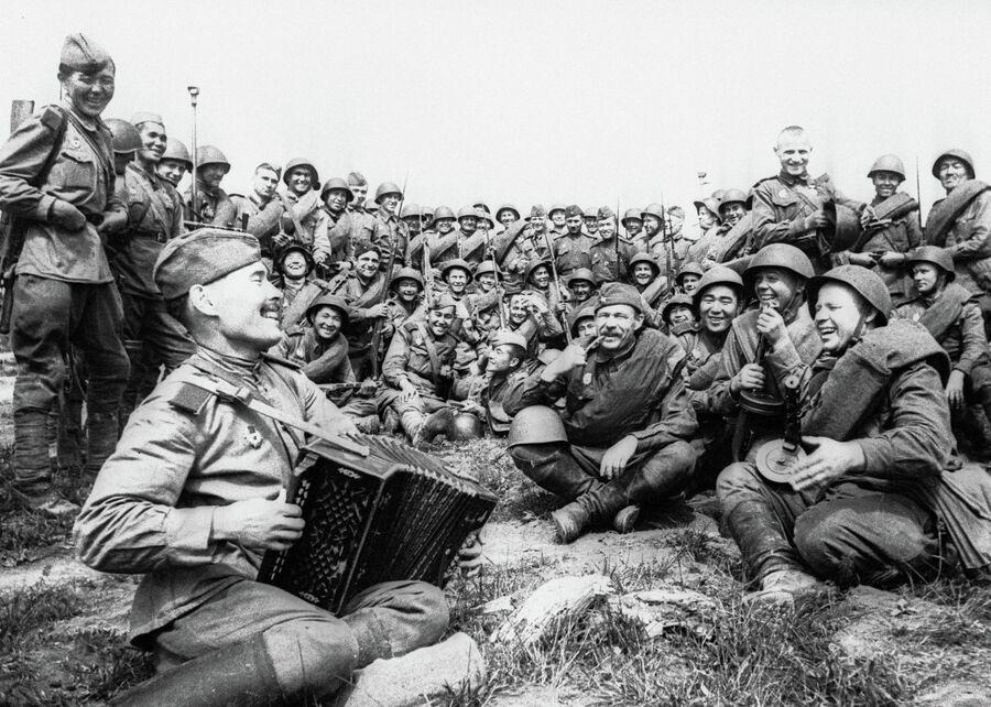 Советские бойцы слушают игру гармониста