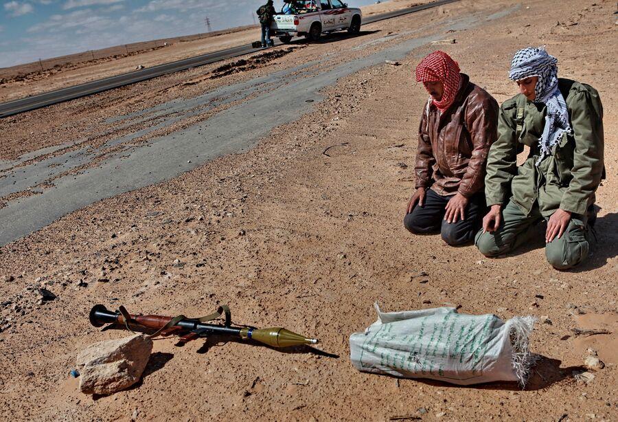 Бойцы молятся на обочине дороги в перерыве между боями за город Бин Джавад