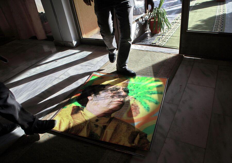Портрет Муамара Каддафи на полу в холле одного из отелей в городе Рас-эль-Ануф
