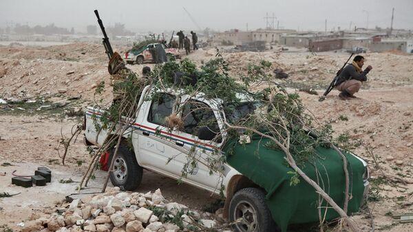 Боец сил ливийской оппозиции у автомобиля с зенитным пулеметом, замаскированный ветками от атак с воздуха, у города Брега