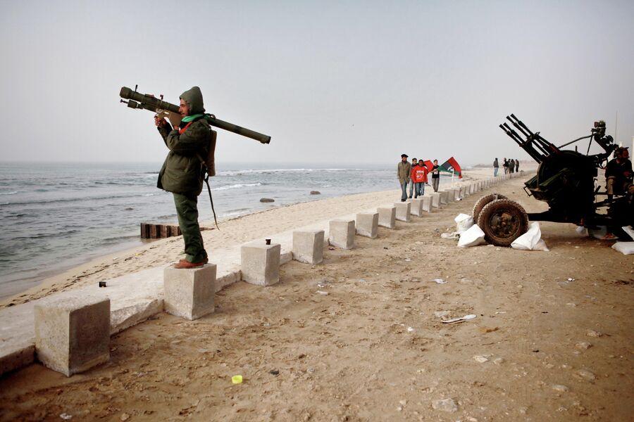 Боец сил самообороны Бенгази с переносной зенитной установкой стоит на набережной Средиземного моря