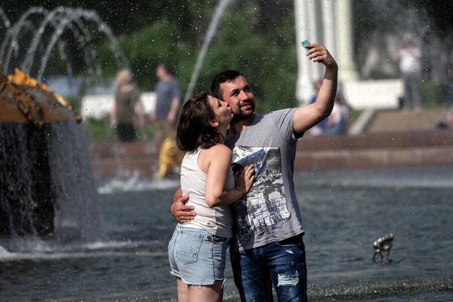 Молодые люди отдыхают у фонтана на ВДНХ в Москве