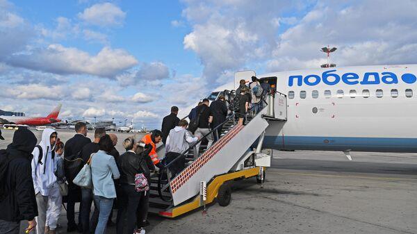 Пассажиры проходят на посадку в самолет авиакомпании Победа в аэропорту Внуково