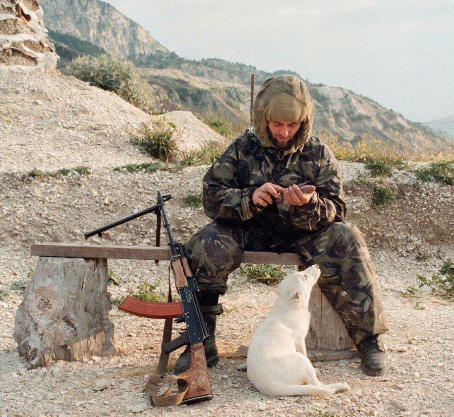 Исламский боевик разрубает еду для собаки на позиции в Ботлихском районе Дагестана