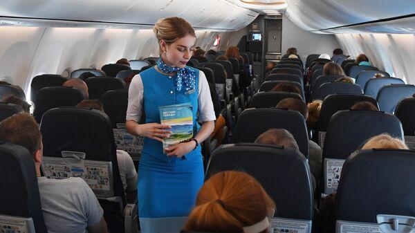 Бортпроводница в салоне самолета авиакомпании Победа, прибывшего в аэропорт Горно-Алтайска