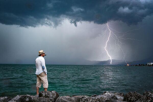 Мужчина наблюдает как молния ударяет в Женевское озеро