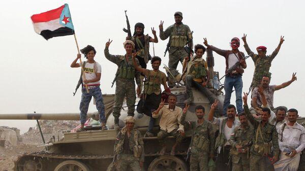 Члены поддерживаемых ОАЭ южно-йеменских сепаратистских сил стоят на танке во время столкновений с правительственными войсками в Адене, Йемен