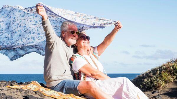 Пожилая пара отдыхает на берегу океана на Тенерифе