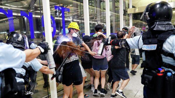 Китайская полиция применяет перцовый спрей для разгона протестующих  во время массовой демонстрации  аэропорту Гонконга, Китай. 13 августа 2019