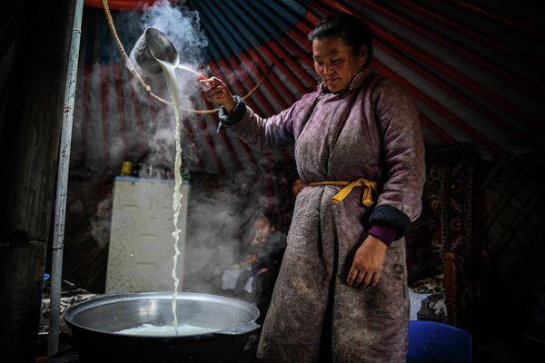 Женщина кипятит молоко в Монголии