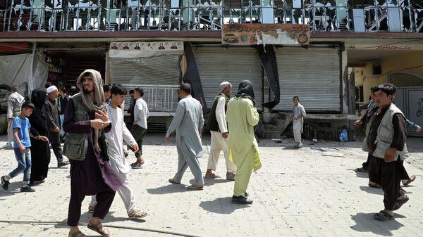 Люди проходят мимо здания с выбитыми окнами на месте взрыва в Кабуле, Афганистан