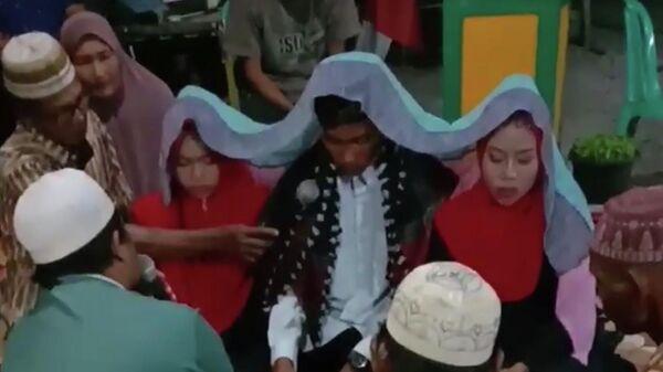 Стоп-кадр свадьбы мужчины и двух девушек в Индонезийской провинции Западный Калимантан