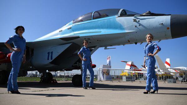 Девушки у многоцелевого фронтового истребителя МиГ-35 на Международном авиационно-космическом салоне МАКС-2019