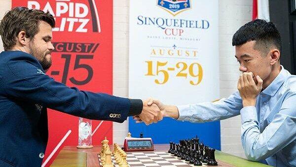 Магнус Карлсен (слева) и Дин Лижэнь