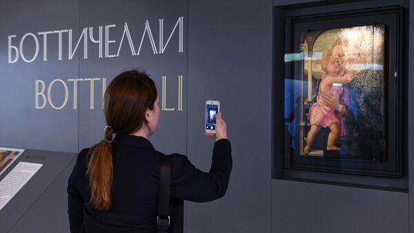 Посетительница фотографирует картину Боттичелли Мадонна делла Лоджиа
