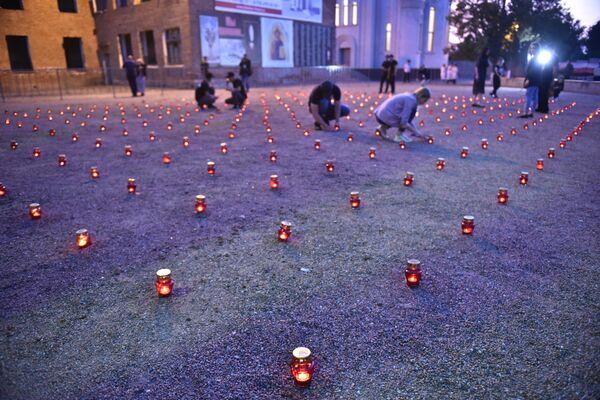 Жители зажигают свечи во дворе бывшей 1-й Бесланской школы в память погибших в теракте 1-3 сентября 2004 года