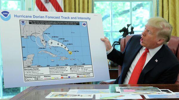 Президент США Дональд Трамп держит диаграмму, показывающую первоначальный прогнозируемый след урагана Дориан