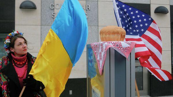 Женщина держит флаг Украины посольством США в Киеве