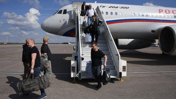Участниками договоренности об освобождении между Россией и Украиной сходят с борта российского самолета Ту-204 в аэропорту Внуково
