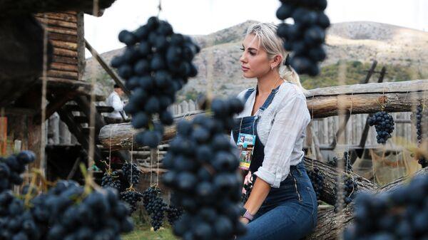 Девушка фотографируется в виноградной фотозоне на Празднике Винограда в интерактивном парке Викинг в селе Перевальное Симферопольского района