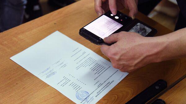 Наблюдатель фотографирует сведения о результатах голосования на избирательном участке