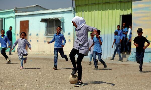 Палестинцы играют в футбол во дворе школы на Западном берегу реки Иордан