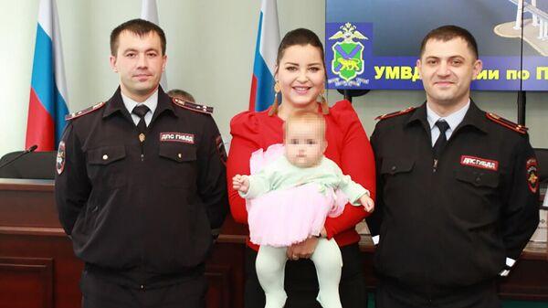Сотрудники полиции Евгений Мельничук и Ариф Мурадханов со спасенной девочкой и ее мамой