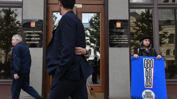 Участница одиночного пикета у здания администрации президента РФ в поддержку актера Павла Устинова