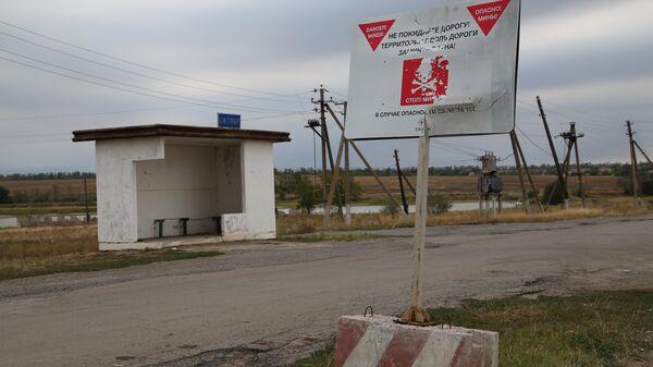 Щит с предупреждением о минах у дороги в окрестностях поселка Октябрь Донецкой области