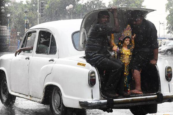 Индуистские преданные перевозят статую Вишвакармана для церемонии погружения в Калькутте