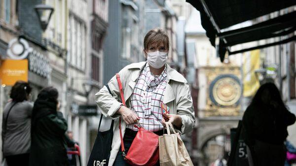 Женщина в маске на улице города Руан,  после аварии на заводе Lubrizol. 26 сентября 2019