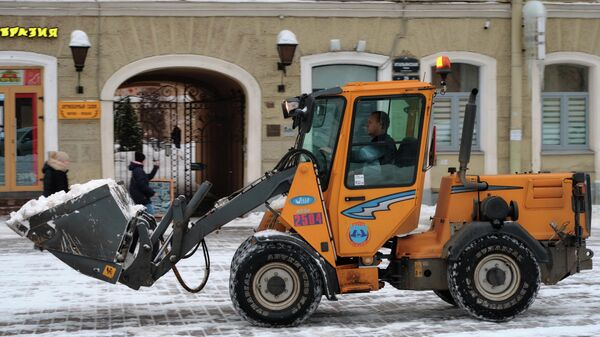 Сотрудник коммунальной службы с помощью спецтехники убирает снег в центре Санкт-Петербурга