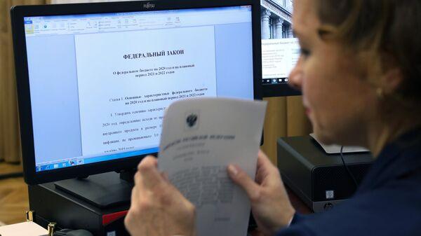 Сотрудник аппарата правительства подготавливает документы и материалы проекта бюджета на 2020-2022 годы