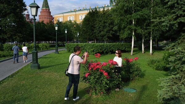 Молодой человек фотографирует девушку в Александровском саду в Москве