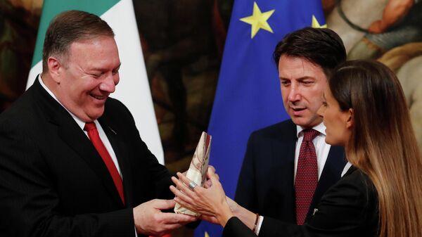 Госсекретарь США Майк Помпео получает кусок сыра пармезан от итальянской журналистки Алисы Мартинелли во время его встречи с премьер-министром Италии Джузеппе Конте в Риме, Италия. 1 октября 2019