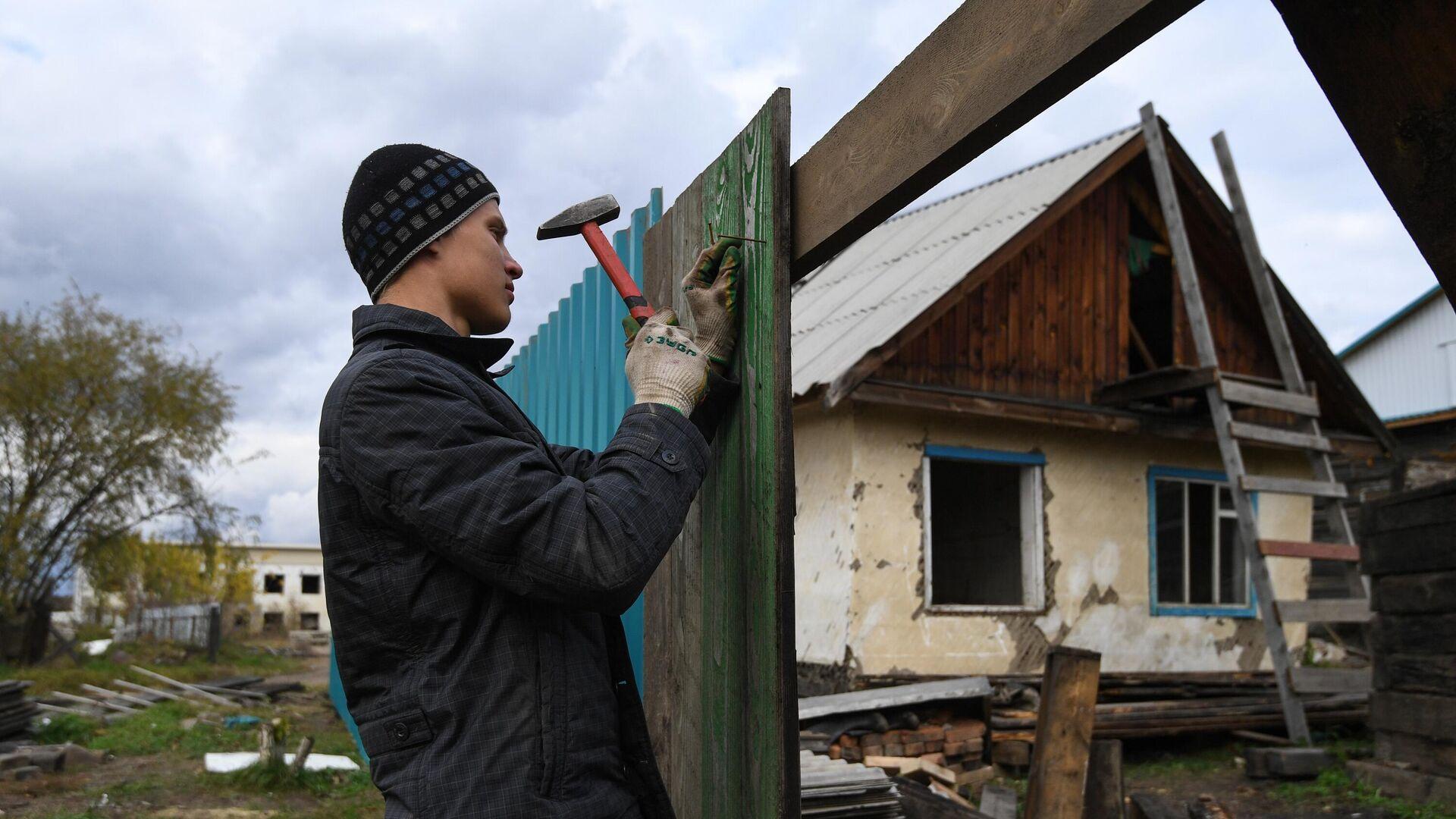 Мужчина ремонтирует забор, поврежденный наводнением в Тулуне - РИА Новости, 1920, 26.06.2020