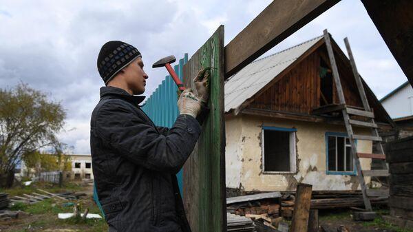 Мужчина ремонтирует забор, поврежденный наводнением в Тулуне