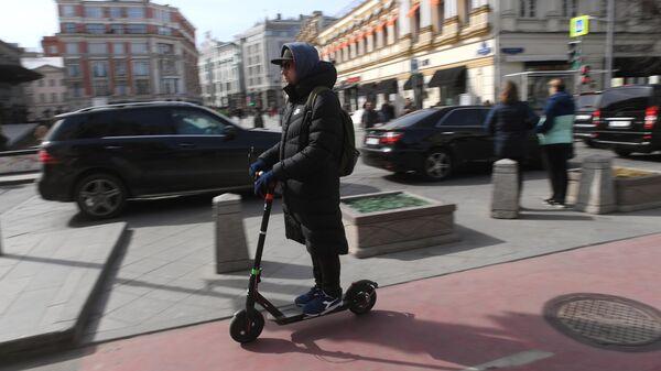 Мужчина едет на электросамокате