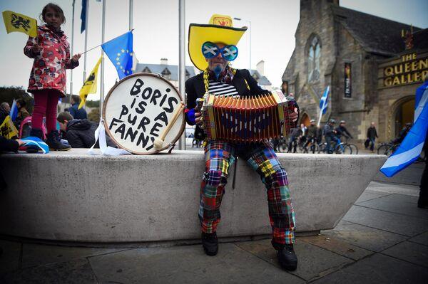 Демонстрант играет на аккордеоне перед маршем за независимость Шотландии в Эдинбурге